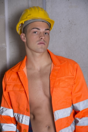 Handsome young construction worker with orange suit photo