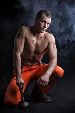 shirtless muscular construction worker kneeling on the floor with big hammer photo