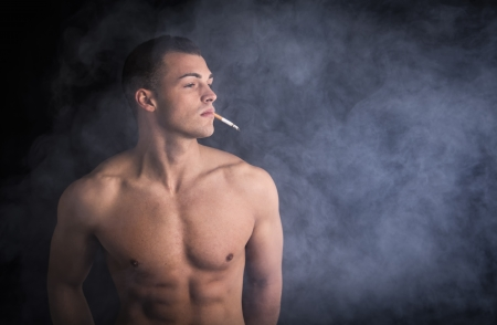 Muscular shirtless young man smoking sigarette with lots of smoke around him photo