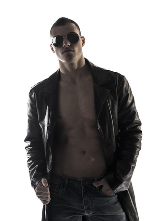 Muscular shirtless young man with leather jacket and sunglasses, isolated on white photo