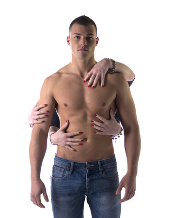 Shirtless, fit young man and four female hands touching him from behind, isolated on white photo
