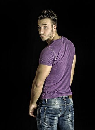 hombres guapos: Hombre joven del ajuste hermoso que se coloca, d�ndose la vuelta, vistiendo camiseta p�rpura y pantalones vaqueros en el fondo oscuro