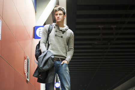 Handsome young man standing in train or subway station looking to a side, shot from below photo