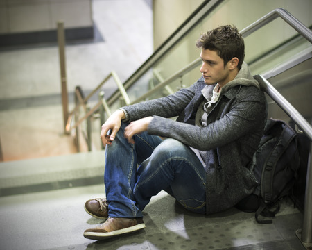 Handsome young man sitting on stairs' marble steps, backpack behind him photo