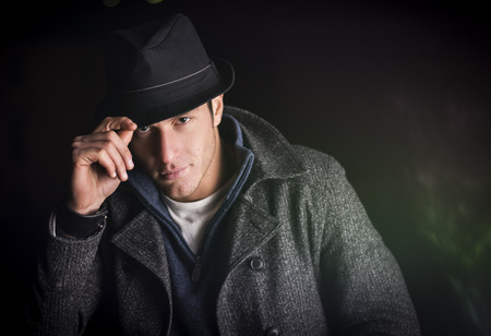 tipping: Attractive young man at night, wearing winter coat, tipping fedora hat while looking at camera Stock Photo