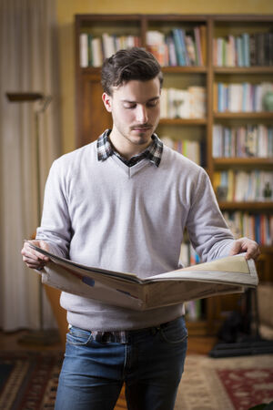 Handsome young man reading newspaper at home in his living-room, standing Stock Photo - 25723784