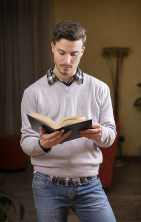 Handsome young man reading book at home in his living-room, standing Stock Photo - 25723786