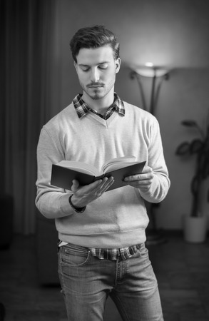 Handsome young man reading book at home in his living-room, standing. Black and white shot Stock Photo - 25723787