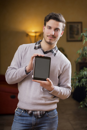 Handsome young man at home in his living room showing tablet PCs screen photo