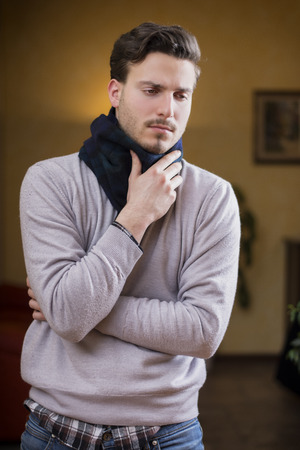 Young man with scarf, holding his neck because of throat ache, at home in his living room Stock Photo - 25723817