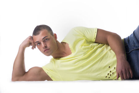 Handsome, muscular young man leaning on the floor, head against his hand photo
