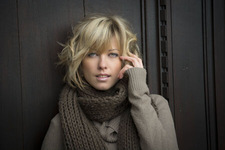 Attractive blonde young woman outside, with winter clothes against wooden door photo