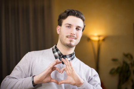 Handsome young man making heart sign with his hands and fingers photo