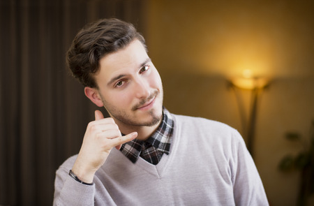 Attractive young man doing  call me  sign with hand and fingers, cheerful expression looking at camera photo