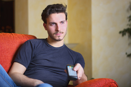 Handsome young man on sofa, using TV remote control and looking off camera  Indoors shot photo