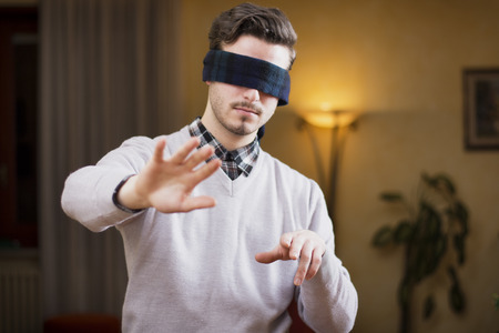 way of living: Blindfolded young man at home in living room cannot see, trying to find his way with his hands Stock Photo