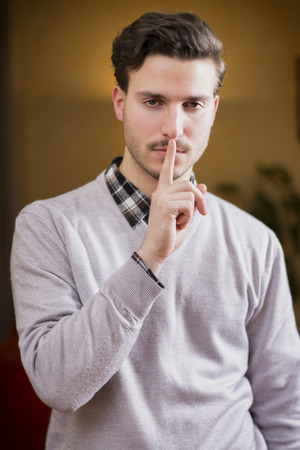 Handsome young man doing Hush sign with finger on lips, looking at camera. On location photo