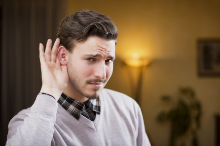 Handsome young man cant hear, putting hand around his ear. Indoors shot inside a house Stock Photo