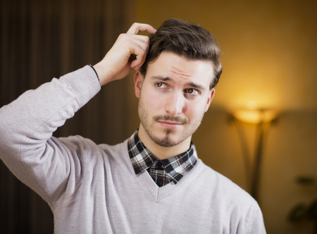 Confused or doubtful young man scratching his head and looking up. Indoors shot in a living room photo