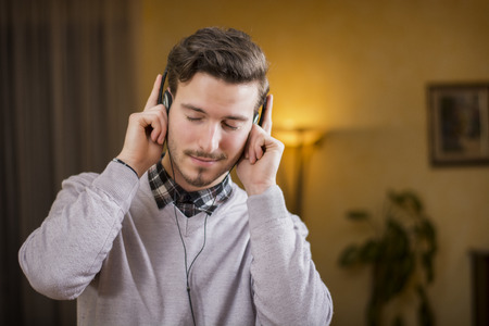 Attractive young man listening to music on headphones, eyes closed. Indoor shot in house photo