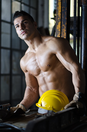 Attractive muscular manual worker shirtless with hardhat looking away photo