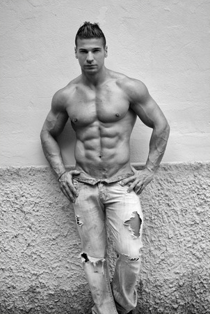 Attractive young man shirtless with jeans leaning against a wall, black and white shot Stock Photo