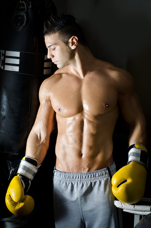 Handsome shirtless young man with boxers gloves in a gym photo