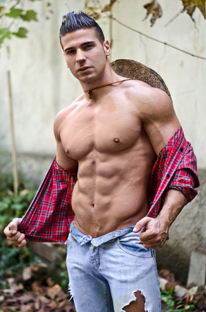 Handsome, muscular young man taking off shirt, wearing jeans and straw hat, outdoors photo