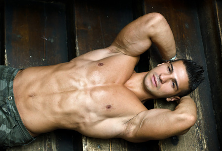 Attractive muscular young man laying on steps of wooden stair, looking at camera, shirtless photo