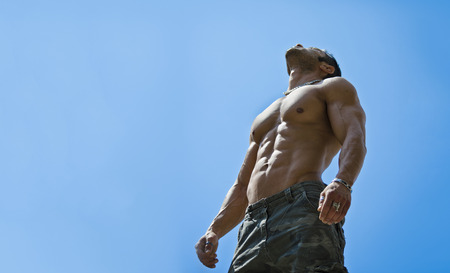 Muscular young male bodybuilder shirtless looking up in the sky, seen from below Stock Photo