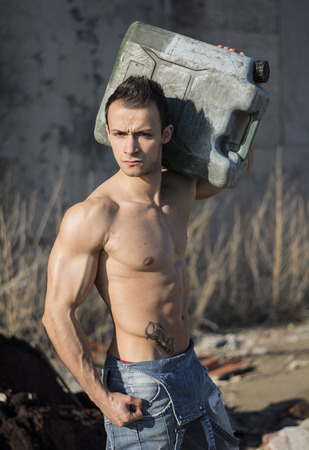 Muscular shirtless young man working. Carrying plastic canister on shoulder, looking at camera photo