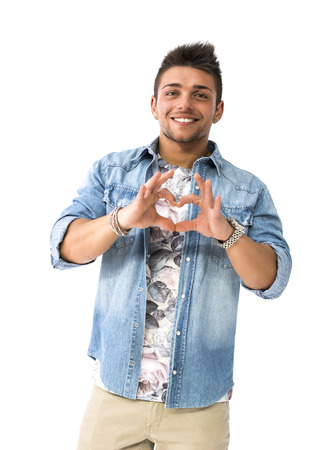 Handsome young man making heart sign with his hands and fingers. Studio shot isolated photo