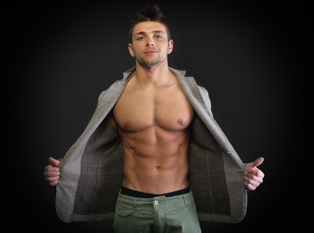Confident, attractive young man with open jacket on muscular torso, ripped abs and pecs photo