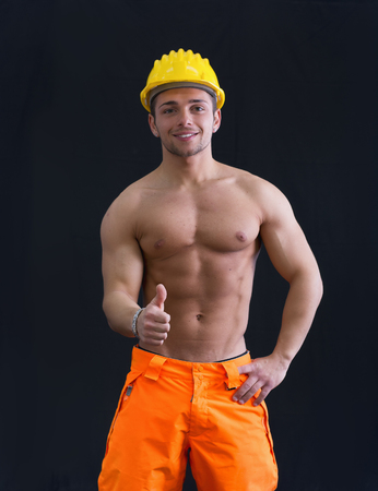 Muscular young construction worker shirtless wearing hardhat doing thumb up sign for OK photo