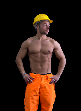 Muscular young construction worker shirtless wearing hardhat, isolated on black