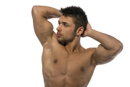 Attractive young muscle man showing athletic torso and biceps, hands behind his head photo