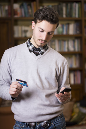 Attractive young man shopping online on mobile phone, holding credit card photo