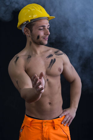 Muscular young construction worker shirtless wearing hardhat, dark background with smoke around photo