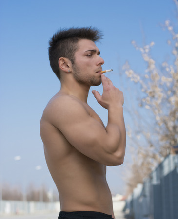 Shirtless muscular young man smoking cigarette outside, standing, profile view photo