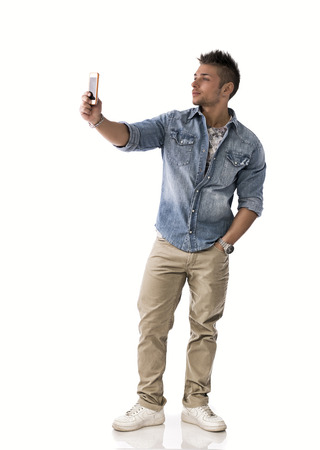 Full body shot of young man taking photo with cellphone, isolated on white photo