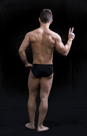 bathing   suit: Back of muscular young man doing peace sign. Full length body shot on black Stock Photo
