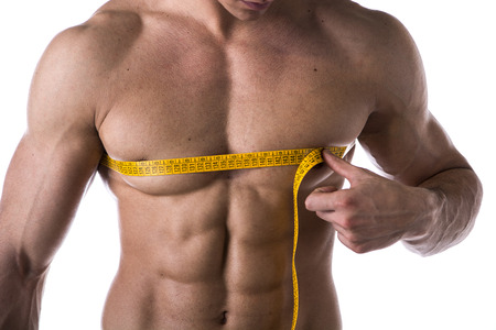 Muscular shirtless young man measuring chest and pecs with tape measure, close-up of torso on white photo