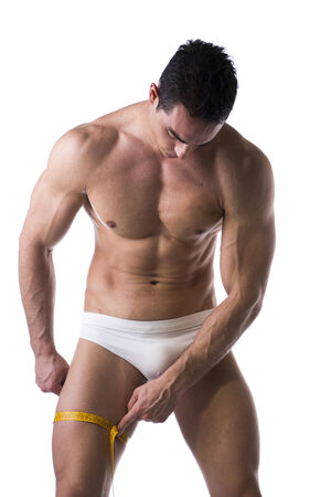 Muscular shirtless young man measuring thigh with tape measure, looking at leg, isolated on white photo