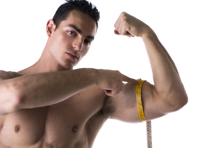 Muscular shirtless young man measuring arm (bicep and tricep) with tape measure, looking at camera, isolated on white photo