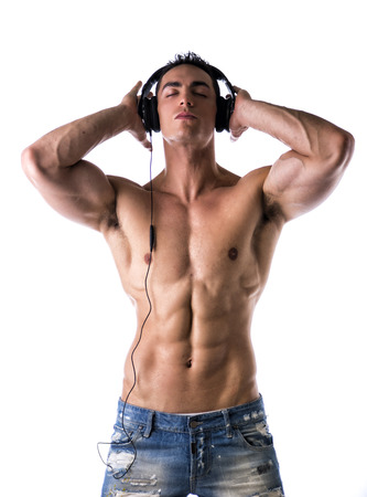 Muscular man shirtless, standing, listening to music on headphones, with eyes closed photo