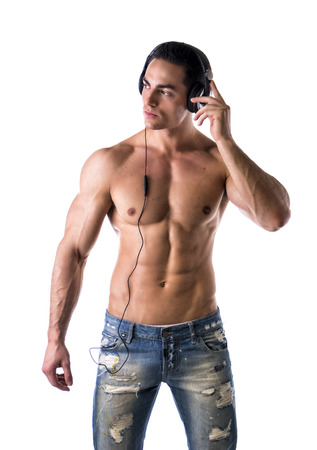 Muscular man shirtless, standing, listening to music on headphones, looking away photo