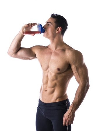 weight: Muscular shirtless male bodybuilder drinking protein shake from blender. Isolated on white, looking at camera