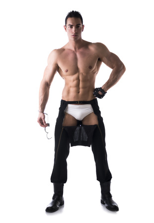 Muscular shirtless young man with handcuffs and studded glove. Full body length shot