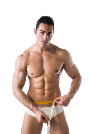 Muscular shirtless young man measuring waist with tape measure, looking at camera, isolated on white photo