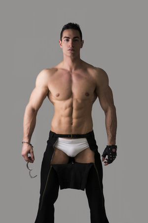 Muscular shirtless young man with handcuffs and studded glove on grey background photo